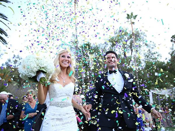 Wedding couple showered with confetti - wendoevents.com
